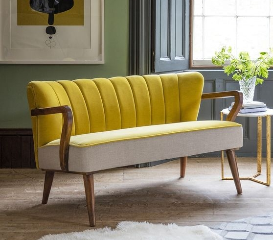 Combining Art Deco styling with a mid-century feel, our Tallulah 2 seater sofa in Mustard Yellow velvet and linen oozes comfort and charm. Big enough for two or even three, this luxurious seating option provides an alternative take on the traditional sofa suite. The scalloped back design in rich blue velvet has an elegant fanned look, with sturdy wooden arms and contoured legs.