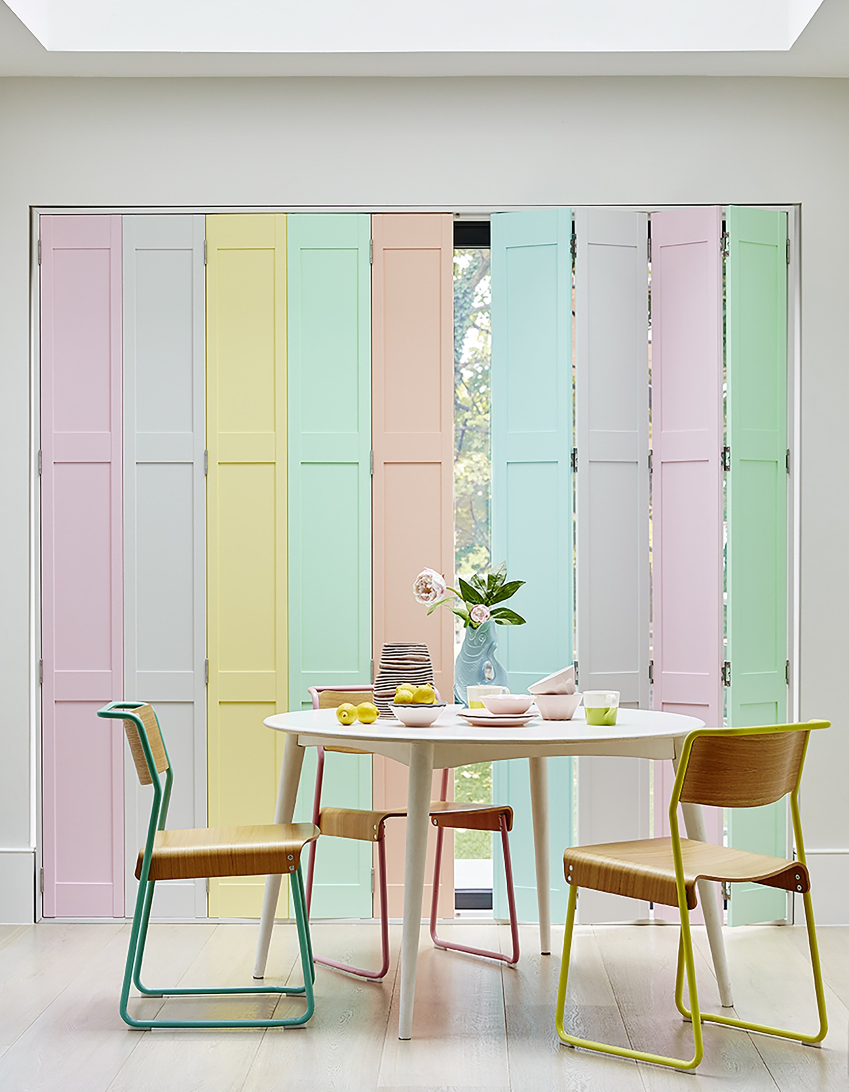 These tracked door shutters in various pastel shades add a real contemporary wow factor to this dining room.