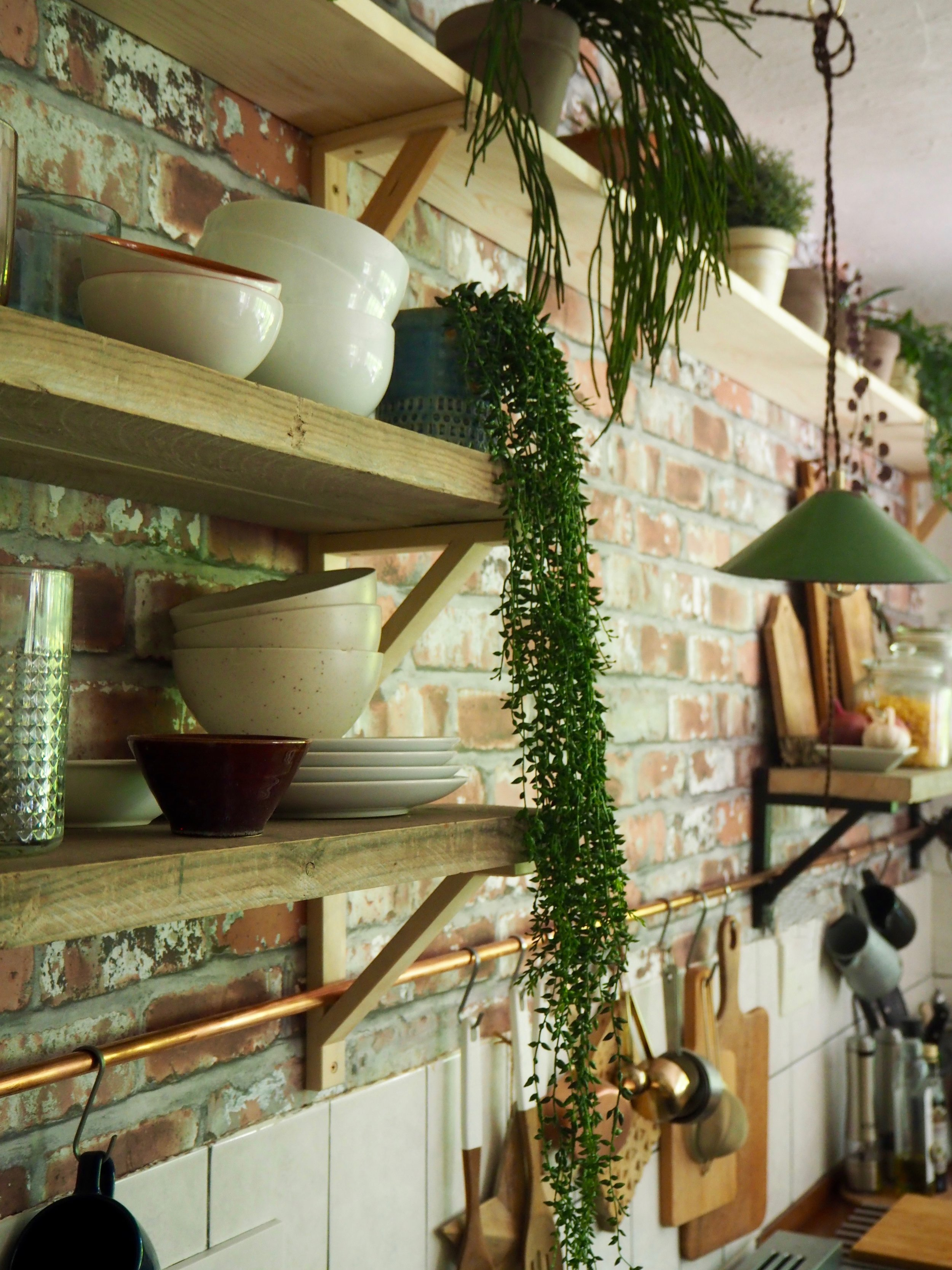 The copper pipe running through the shelf brackets forming a rail…..