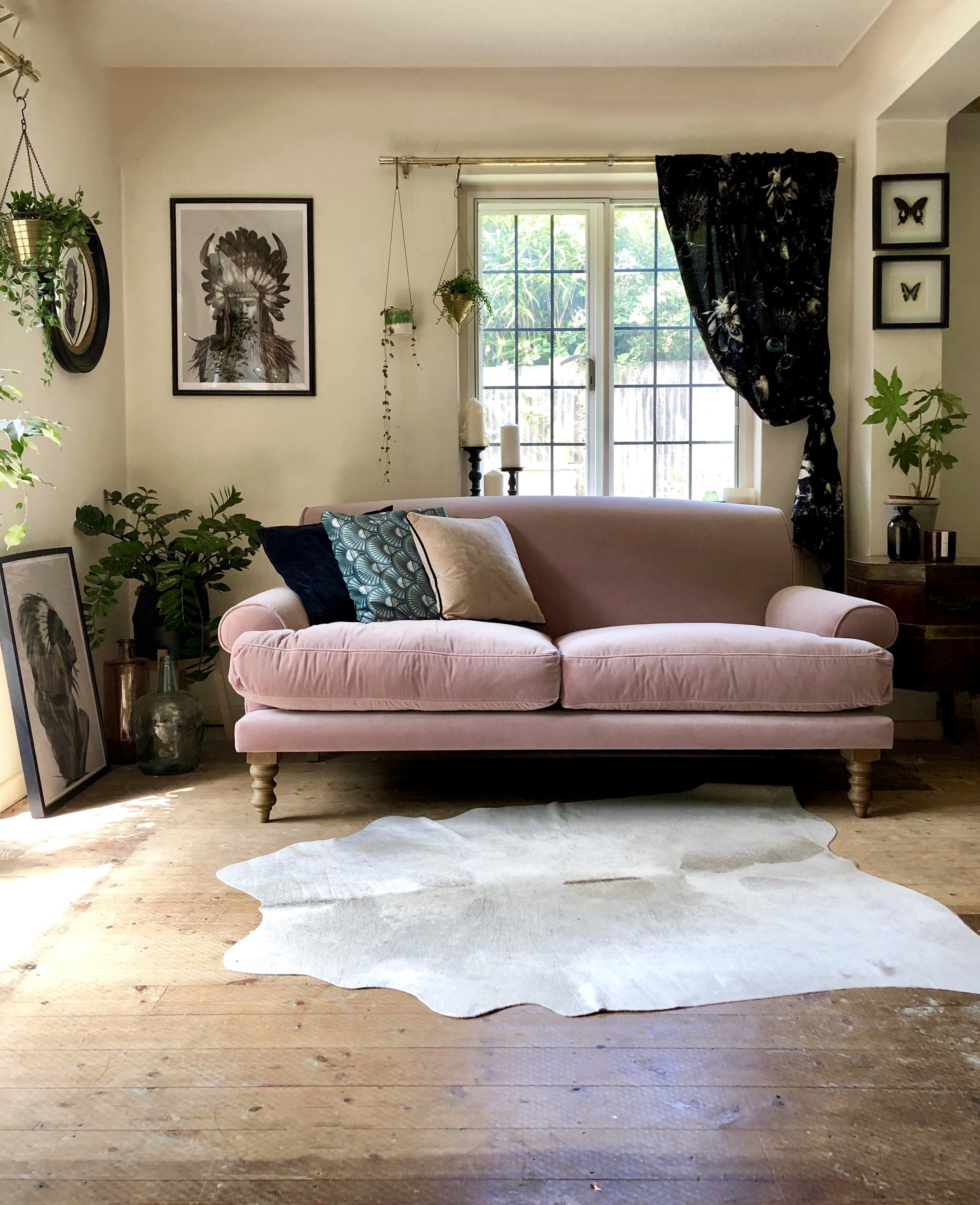 The pink sofa really stands out against the darker accessories…..