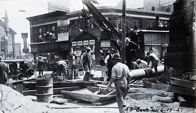 On this day in 1927, workers build brick manholes and excavate a trench at the crossing of Troy and Westminister Street, Olneyville. King's Cathedral Church (then known as Church of the Messiah) can be seen on the right.  This work connected the West End and Downtown Providence to the water supply at Neutaconkanut Hill.