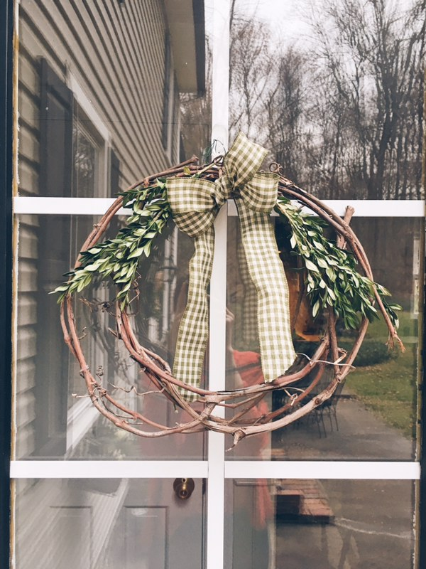 An easy way to dress up a branch wreath, with a bow and some winter leaves.