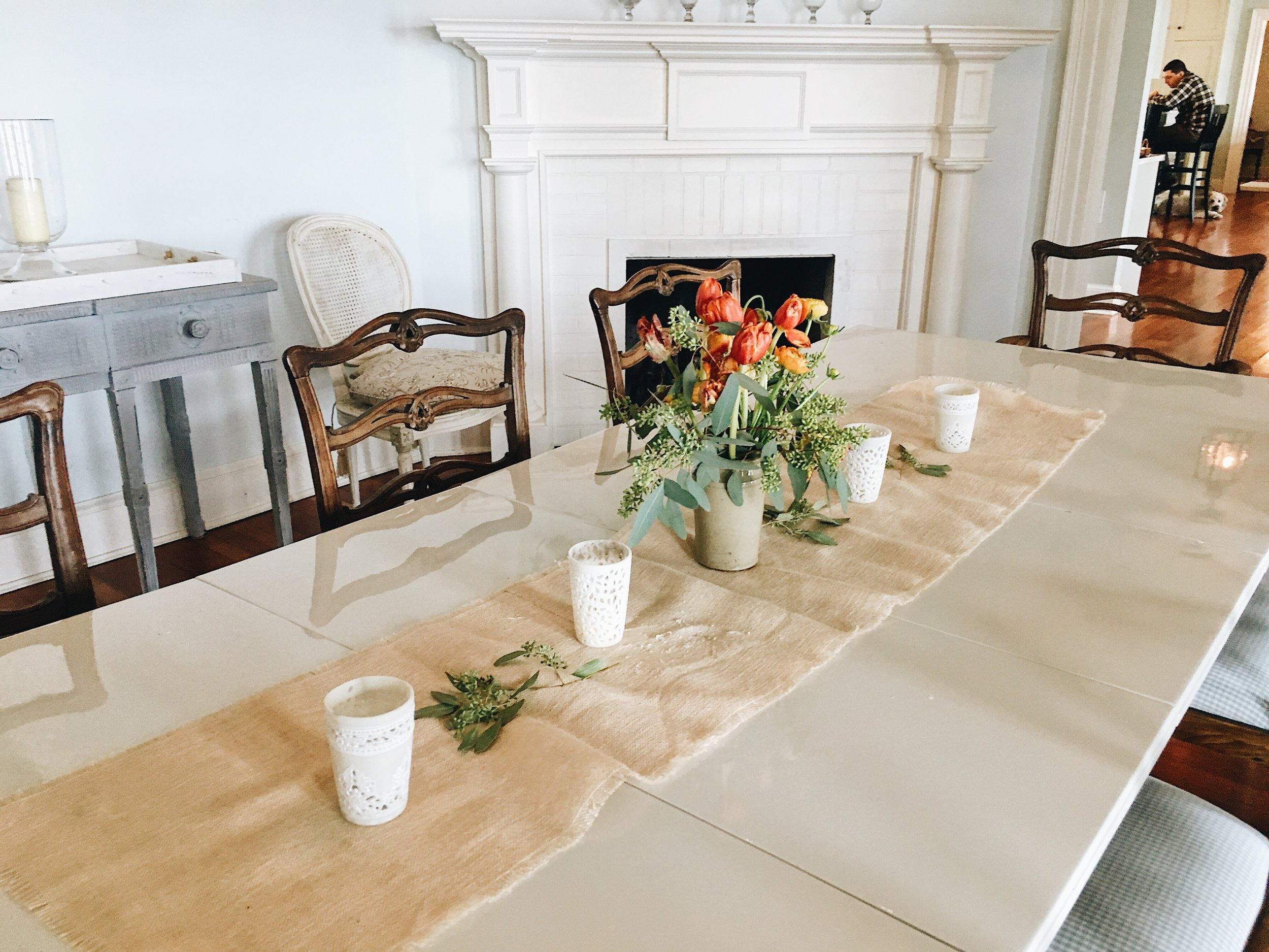Pretty orange flowers and green leaves with a rustic table runner for entertaining.