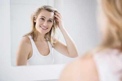 Lady looking in the mirror after having Botox at David Vaughan Dental