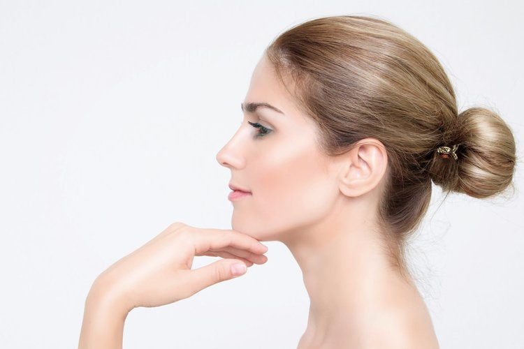 Lady with beautiful skin touching face after botox treatment