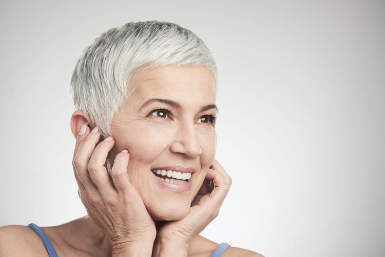 Attractive older enjoys more youthful appearance after dental implant treatment