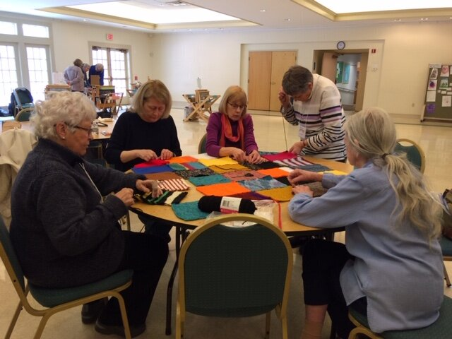 Guild Members working hard on sewing blanket squares.