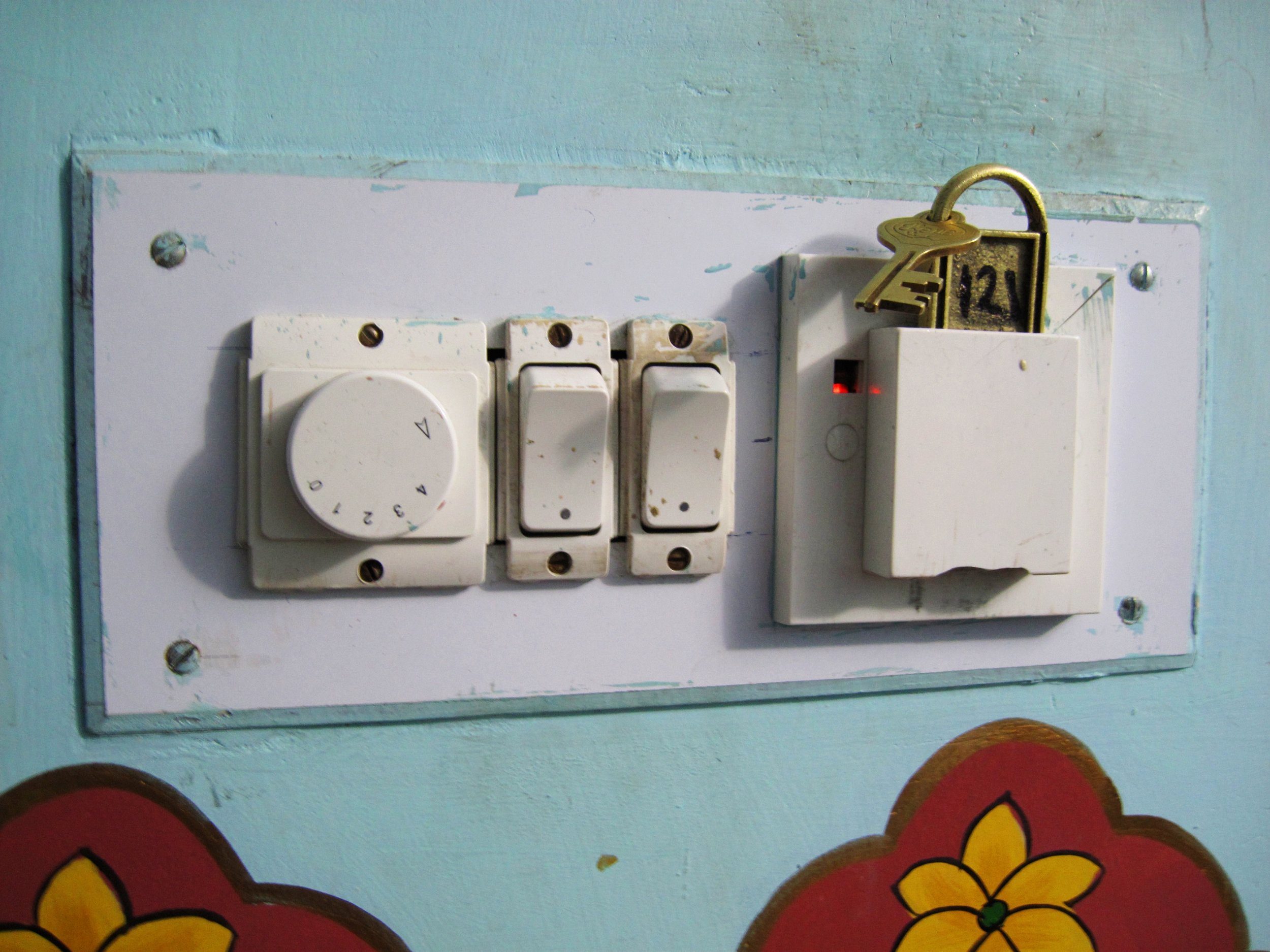 electricity-activating key jodhpur, India - Ingenious device to incentivize people not to lose their keys. No key, no lights. No TV. No Internet. Eva couldn't figure out why the metal key didn't electrocute her when she inserted it into the slot. Does anyone know the answer to this?