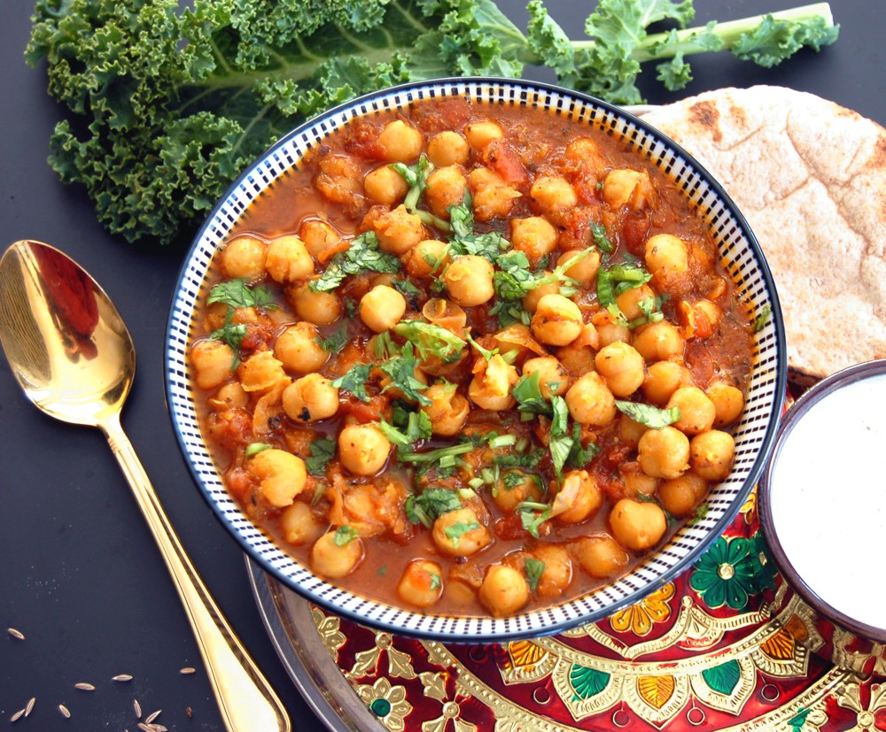 CHANNA MASALA - Sweet & Tangy Chick Pea Curry - {Made with Arvinda's Curry Masala}A vegetarian Indian delight! Earthy chick peas (garbanzo beans) immersed in an aromatic tomato and onion curry sauce. This recipe is a tangy and sweet version that pairs best with basmati rice or naan. Leftovers are ideal on top of a salad with a raita yogurt dressing or stuffed into a wrap or pita pocket for a quick lunch. Channa Masala is quick enough to prepare so that it can easily make its rounds in your repertoire of weekly meals.
