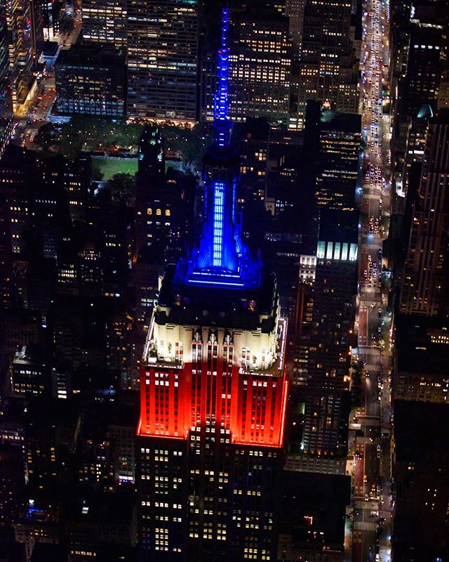 The ESB in all its patriotic glory — with a little hint of a glowing Bryant Park. That's Fifth Avenue on the right looking uptown. #🚁 #esb #empirestatebuilding