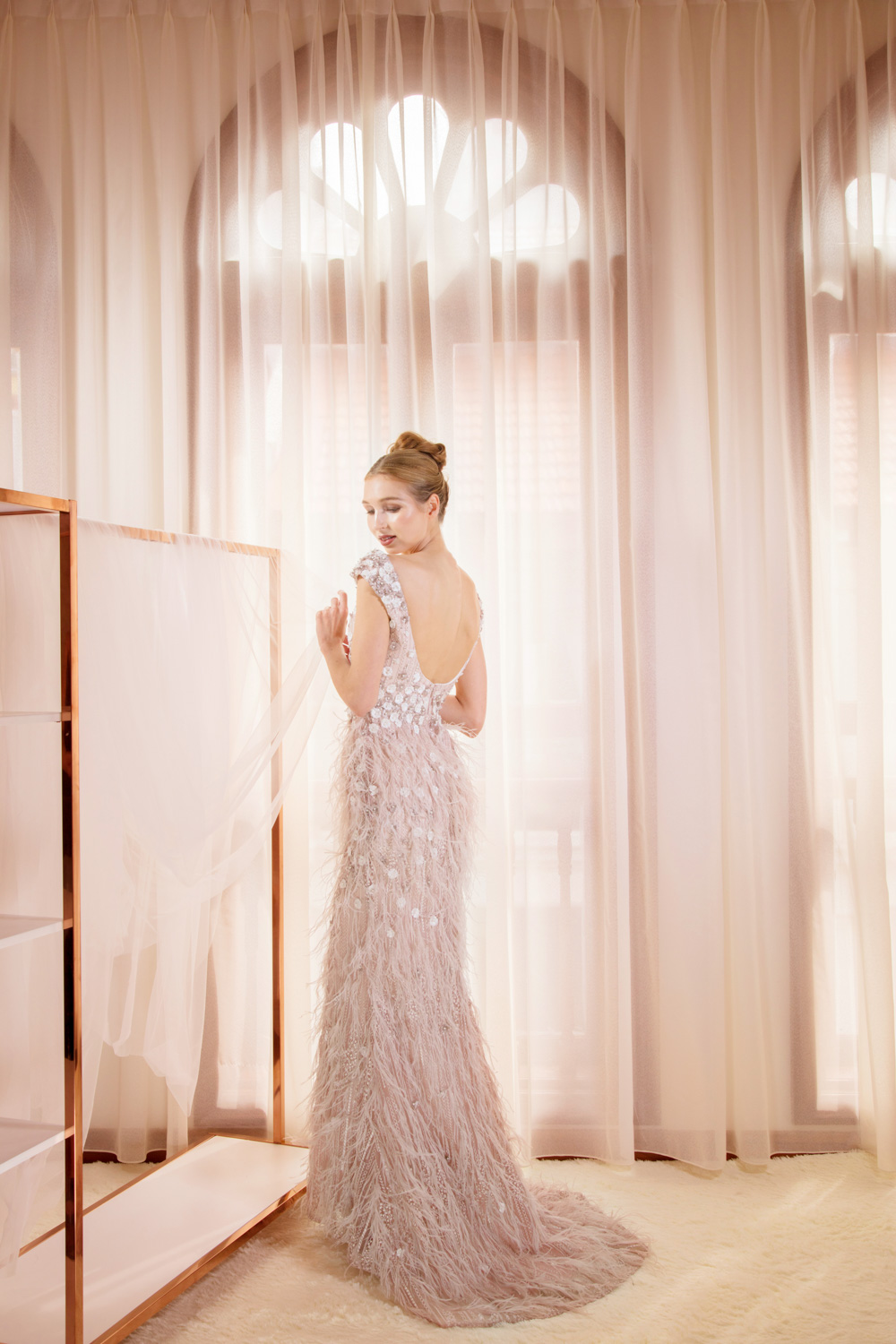 Evening gown with low back and feather detail by CCM Wedding