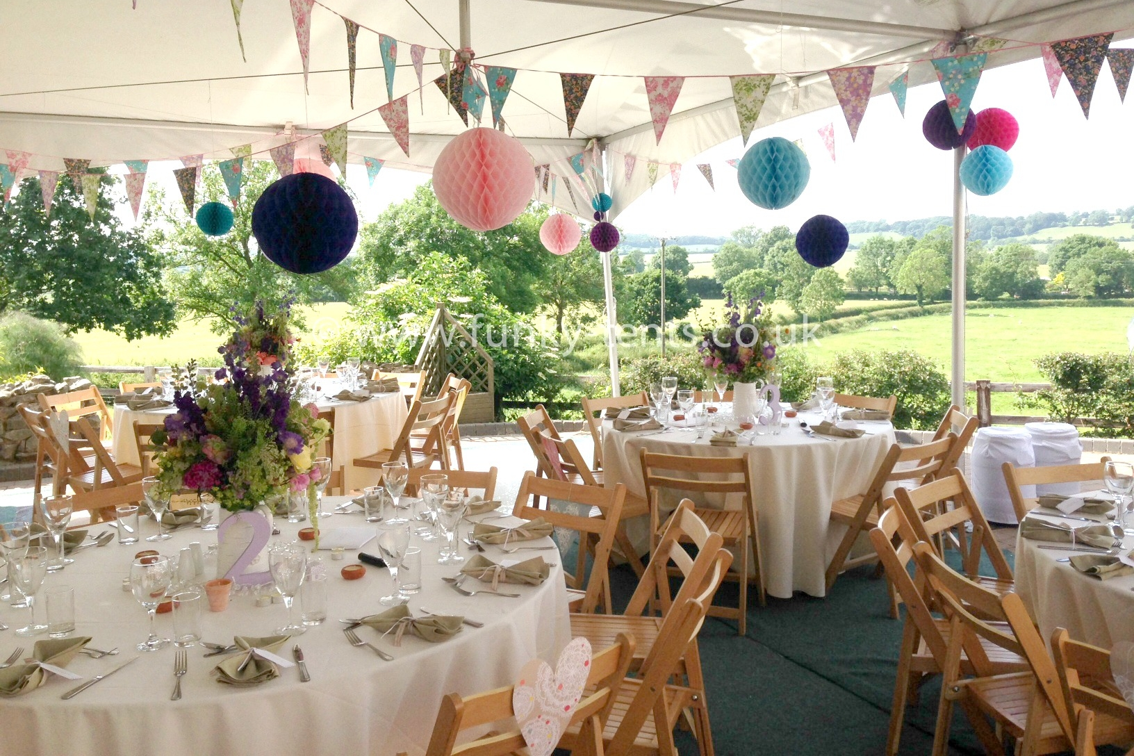 A 20ft x 30ft Matrix marquee with bunting & retro wooden chairs. Open sided for a summer lunch