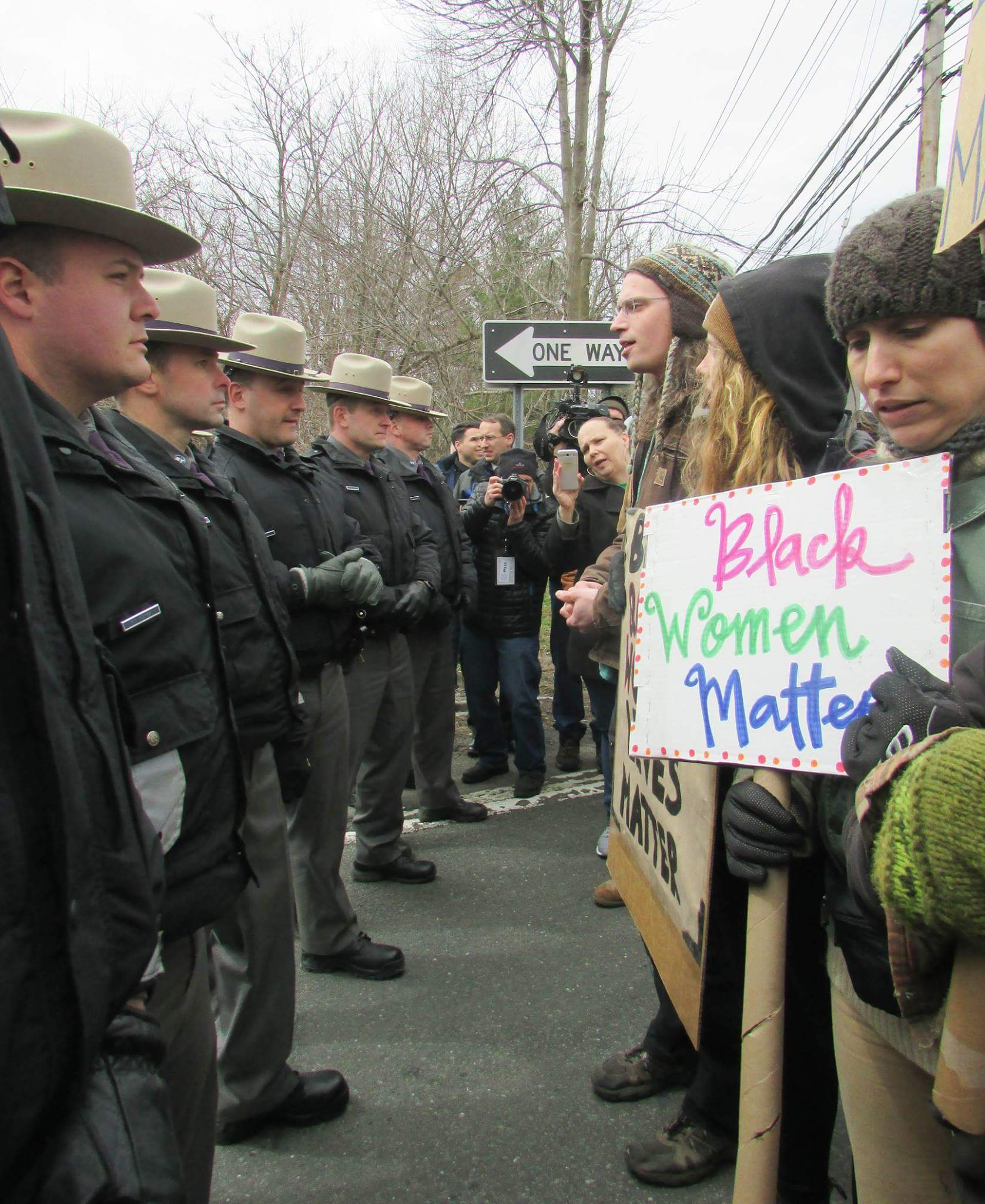 "Photo of marchers on the right, facing a line of state troopers on the left. ""Black Women Matter"" sign."