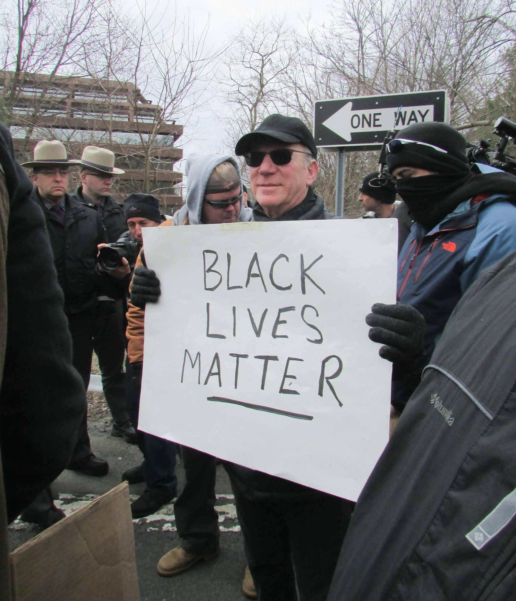 "Photo of white man holding ""Black Lives Matter"" sign. State Troopers are in the background."