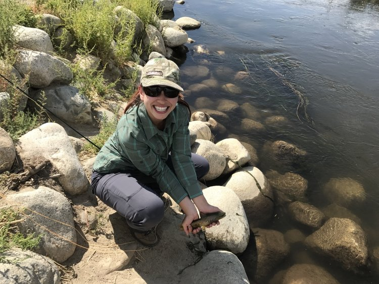 New fly fisher Chelsea Kaplan holds a brown trout she took out of a canal in Bishop.