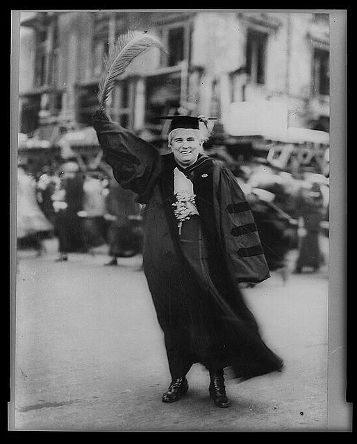 Anna Howard Shaw, full-length portrait, standing, facing front, wearing academic robe and holding large feather