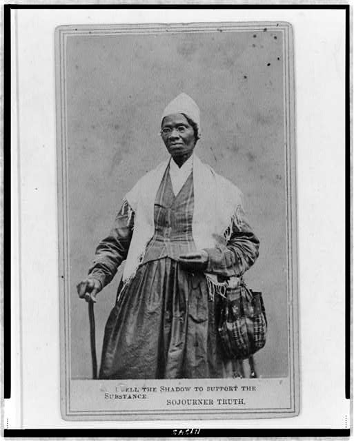 Sojourner Truth, three-quarter length portrait, standing, wearing spectacles, shawl, and peaked cap, right hand resting on cane