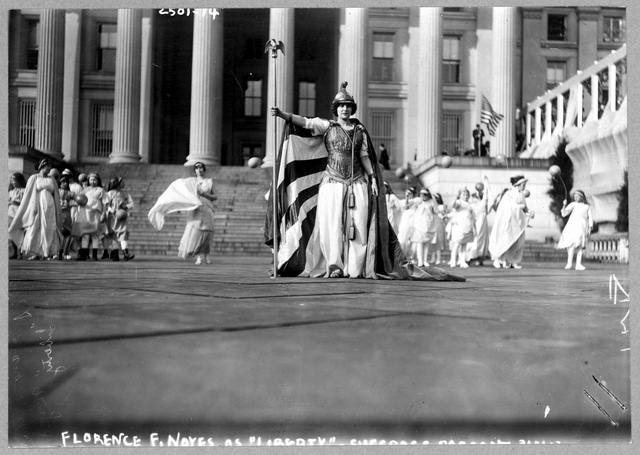 """German actress Hedwig Reicher wearing costume of """"Columbia"""" with other suffrage pageant participants standing in background in front of the Treasury Building, March 3, 1913, Washington, D.C"""
