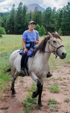 Ginger rides Sax, Cloud's brother, near her ranch below Gibbs Peak in the Sangre de Cristo Mountains of southern Colorado. Sax was removed in 2009 from his Pryor Mountain home and is co-owned by Ginger Kathrens and Ann Evans. Photo by Nadja Hallstrom