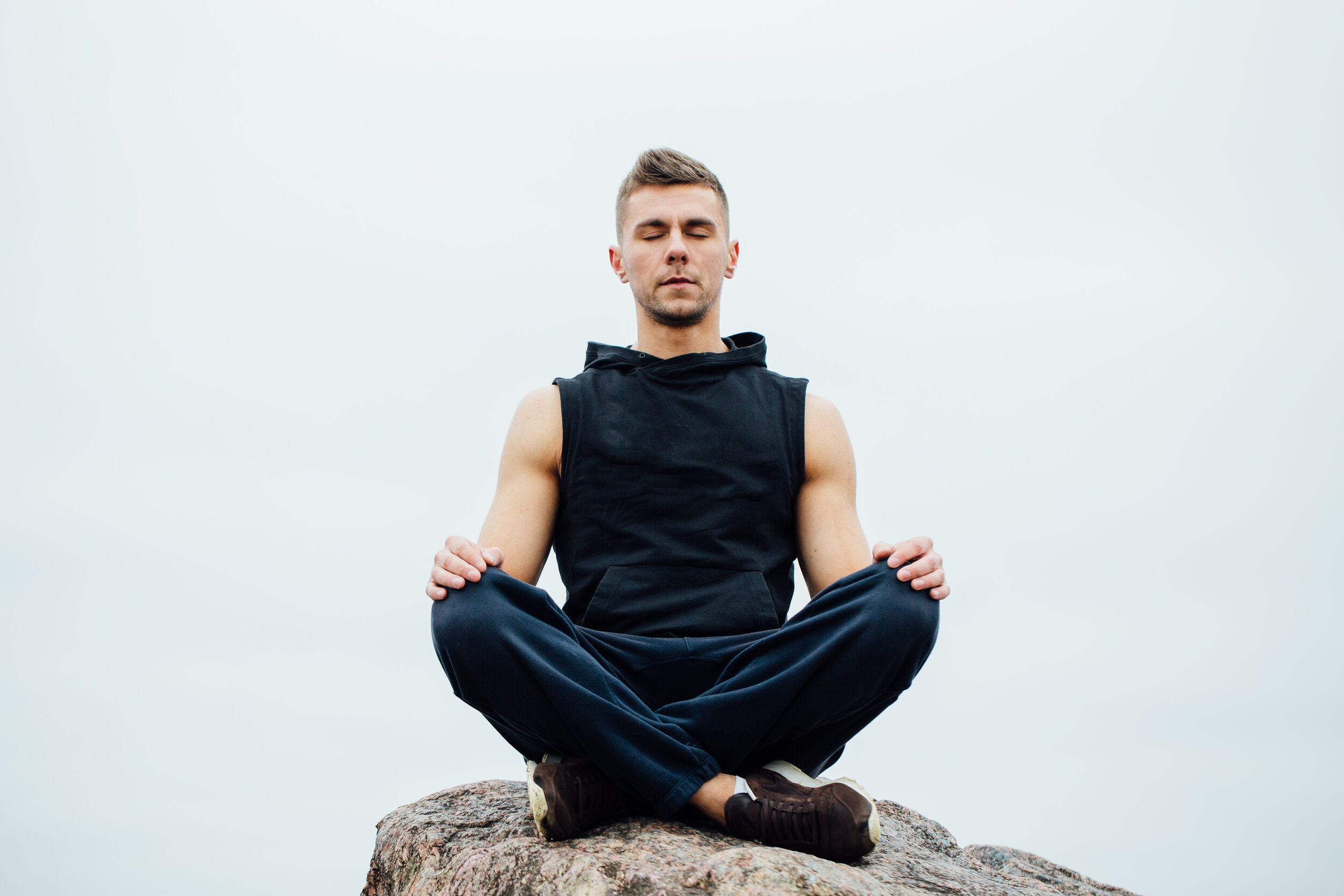 Copy of Strong fitness yoga man in lotus pose on the rock beach near the ocean. Harmonic concept.