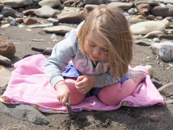 Eloise is drawing a picture in the sand here but desperately did not want to get her pants wet so we had to lay down a blanket for her