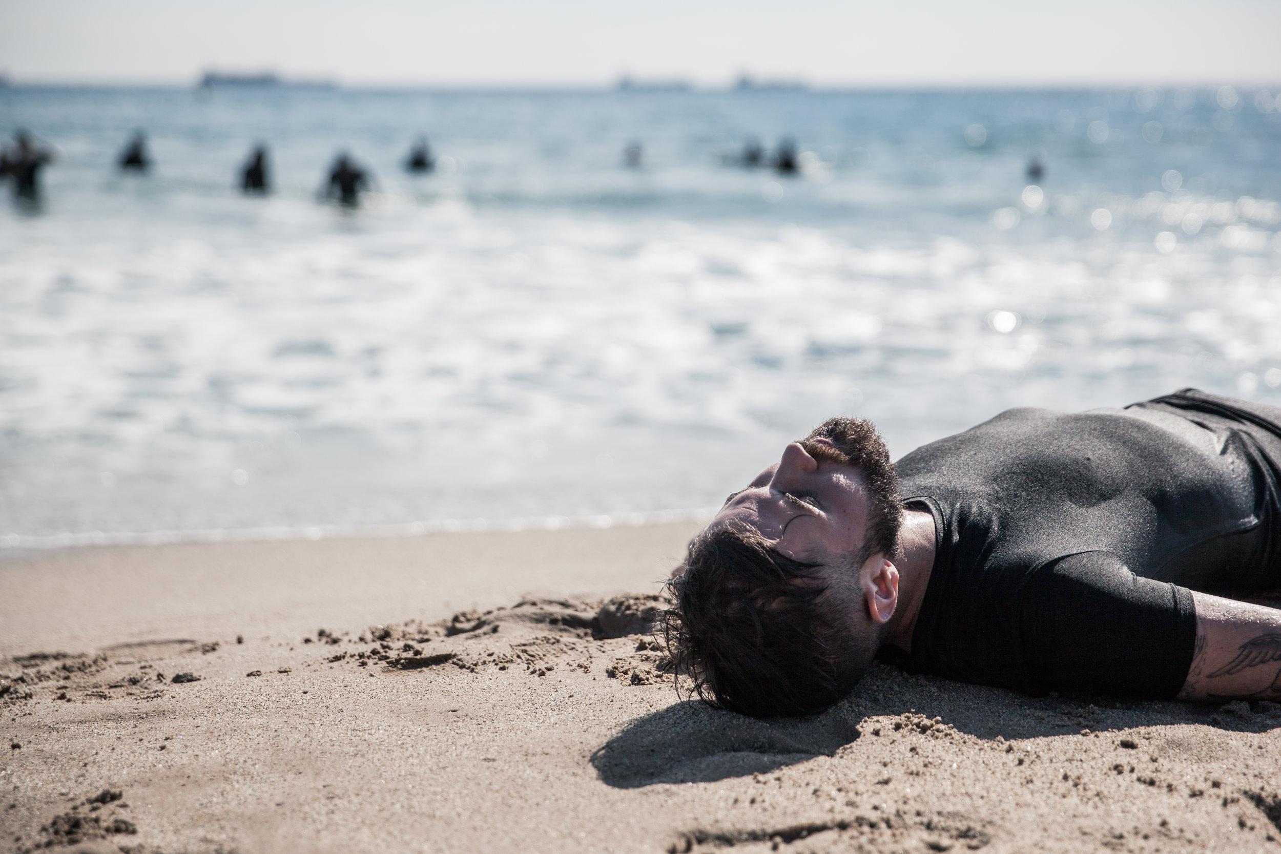 El artista    Abel Azcona    retratado en una de las playas del    Mar Mediterráneo    como    Tarragona   ,    Marsella    o    Palermo    donde realizó la performance El Milagro, la acción crítica con la indiferencia de los países europeos ante la crisis de los refugiados.