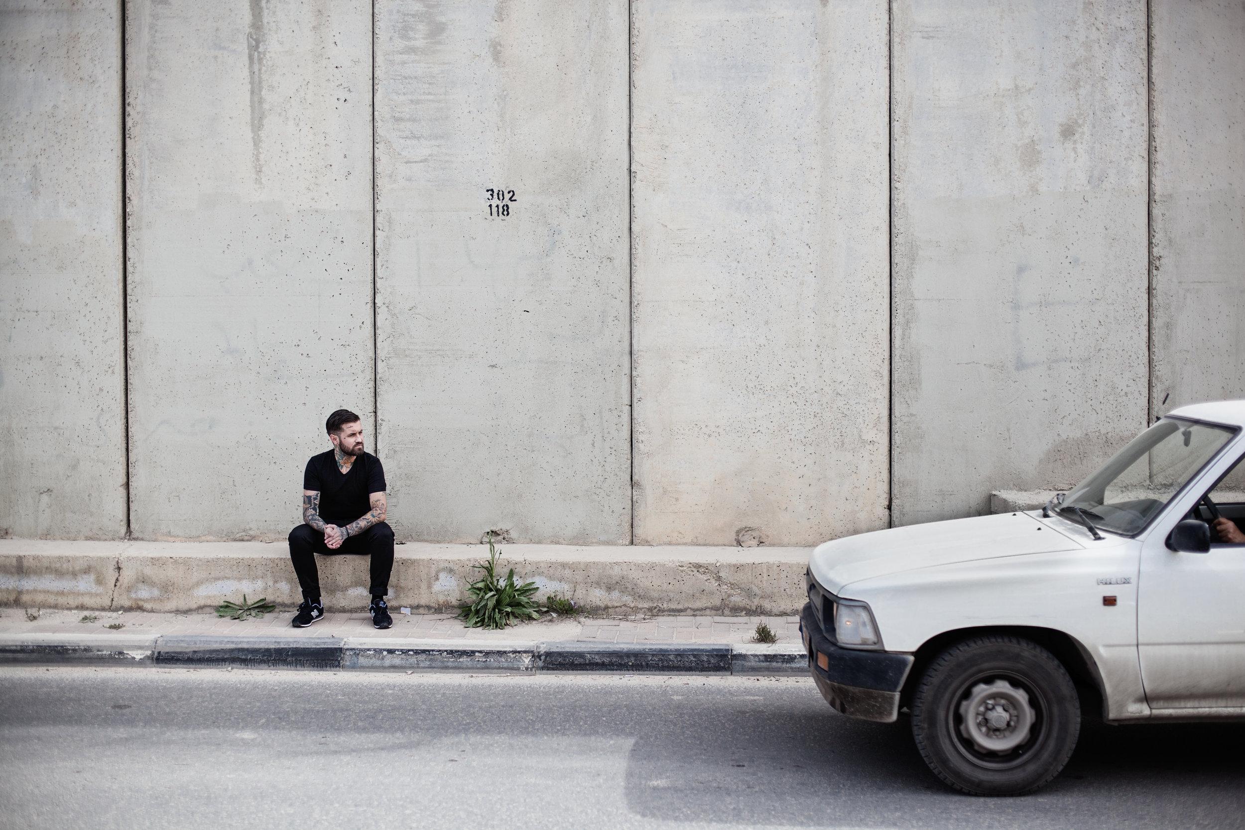 El artista    Abel Azcona    sentado a la entrada de    Ramallah   , durante el proceso de instalación de su obra La Vergüenza a lo largo del muro de    Cisjordania   . Fragmentos del muro de    Berlín    en los resquicios del muro construido por el Gobierno de    Israel   .