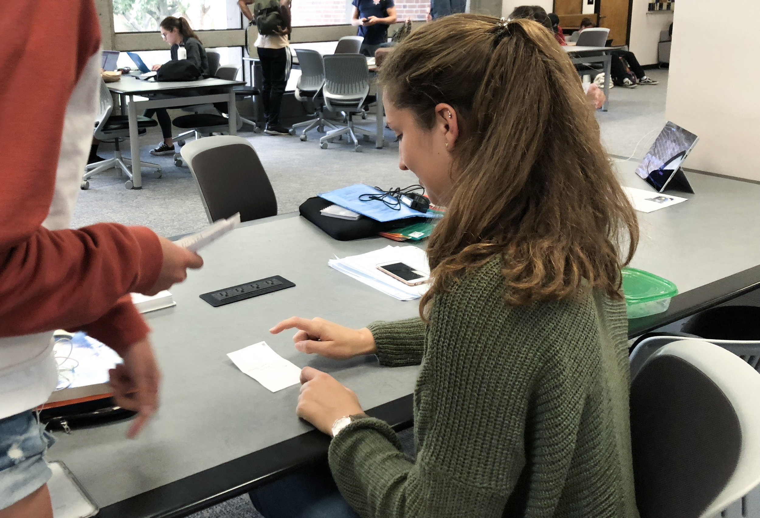 Paper prototype being tested. The test involved one group member giving the user an objective, one member swapping the pieces in response to what the the user 'clicked' , and one member observing and recording how the user interacted with the design what parts were unclear.