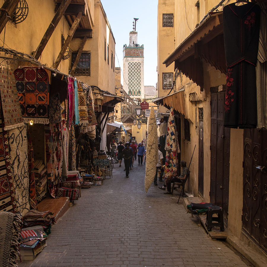 "Typical street in the Medina (old City) of Fes, looking towards a minaret at the Mosque Moulay Idriss II, who claims the title of Founder and Leader of Fes, along with his father in the late 700's. Each of the small doors along the alleyway lead to small ""studios"" where craftspeople often make and sell their goods. Some of these shops are the size of a large closet in the US, but provide all the space needed to make shoes or carve wood. Many are simply ""storefronts"" where merchants sell goods made elsewhere in Fes."