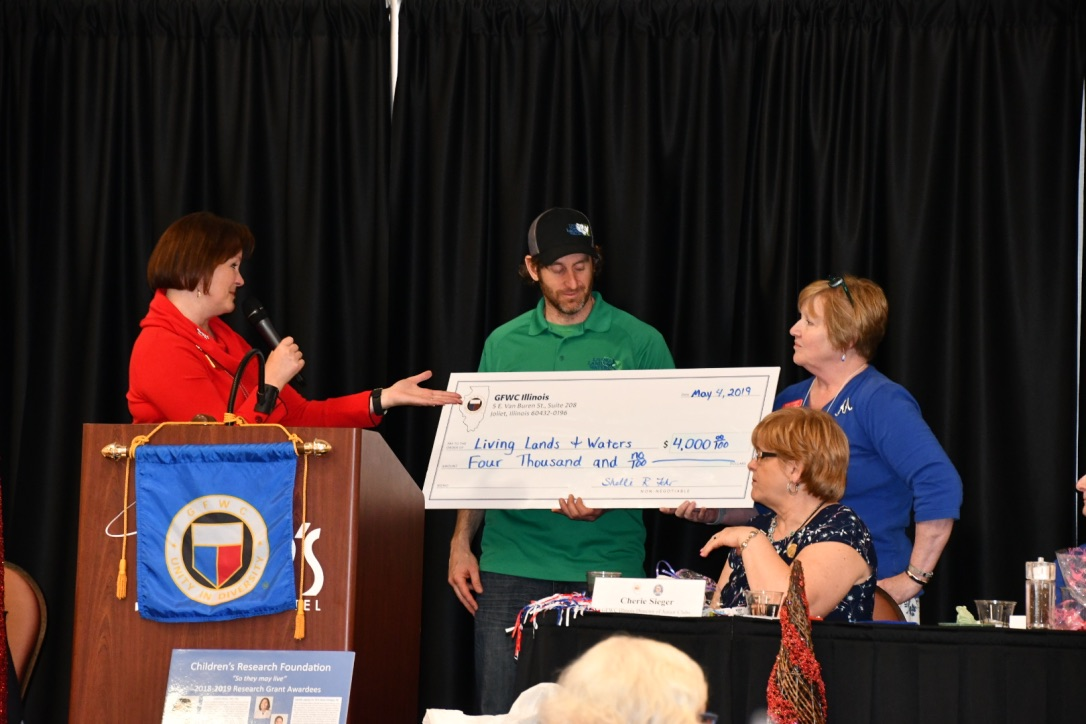 GFWC IL President Shelli Fehr (left, in red) Along with Conservation Chair Diane Addante (right, in blue) Present a $4000 donation check to guest speaker Mike Coyne-Logan (center, in green) with Living Lands and Waters, a non-profit located in East Moline, Illinois.  https://www.livinglandsandwaters.org/