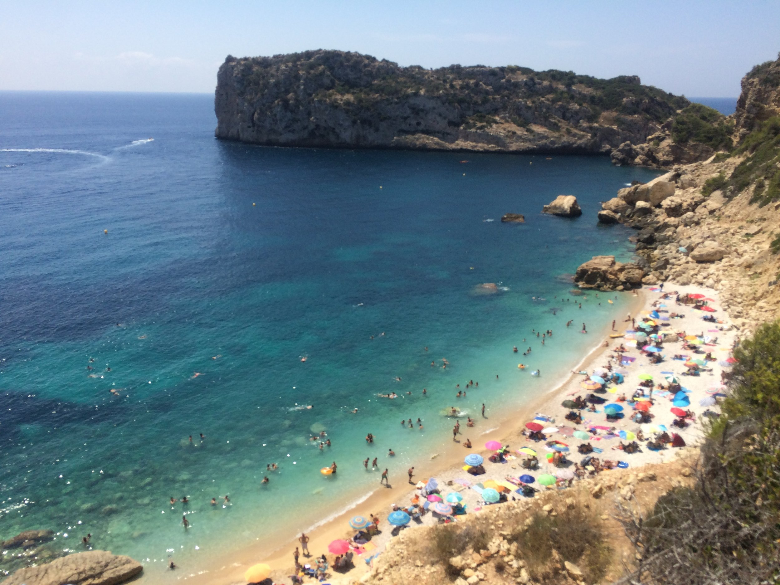 """- Cala Ambolo is known for its crystal clear water for those who are """"in the know"""" in Javea. While you need a car to get there, the trip is always worth it for the views and also a quick beach photo op. No matter where you're capturing some images, they'll be breathtaking. Although be careful while taking photos on the beach because it's a nudist beach and can sometimes get quite crowded during the summer months."""