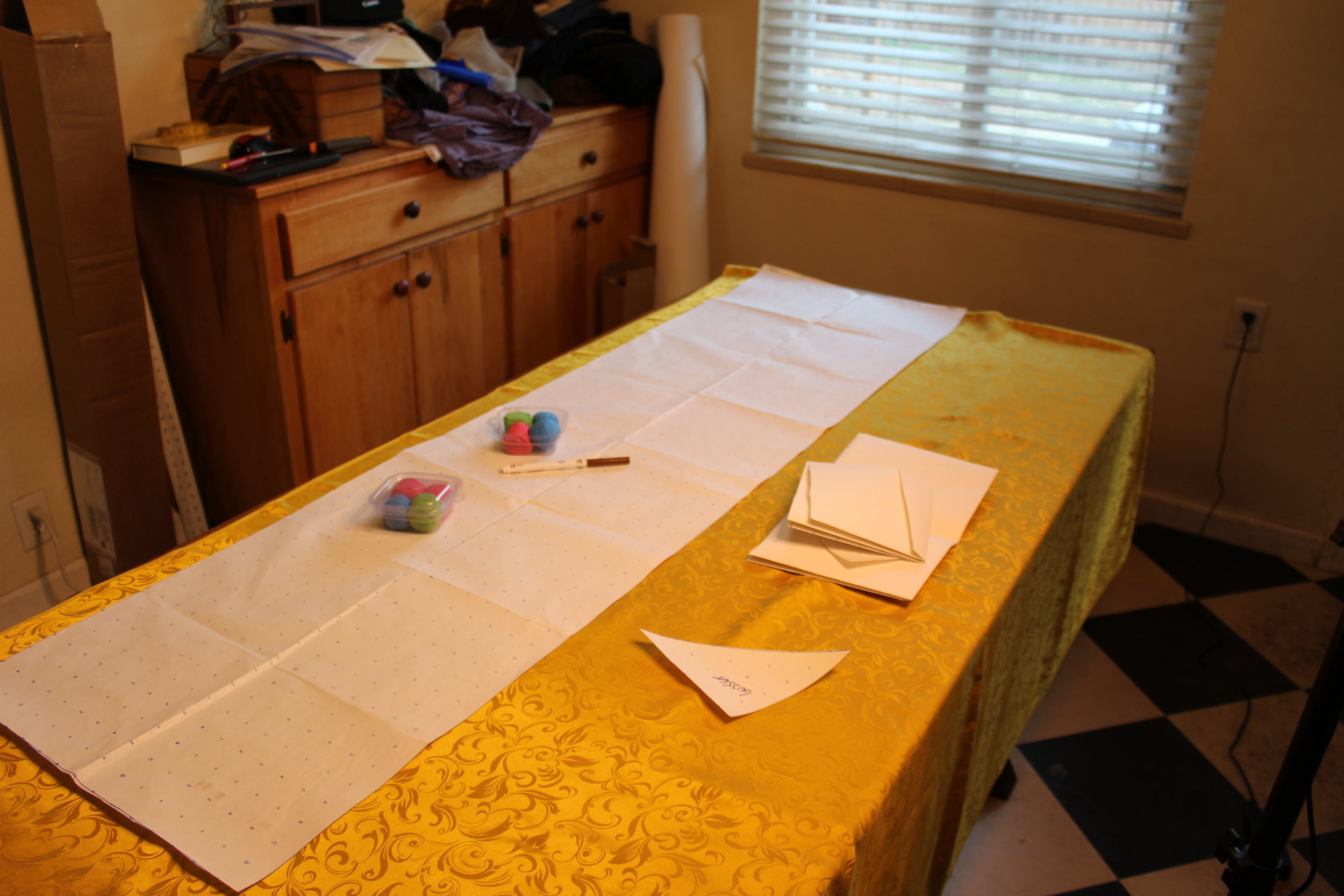 Folded cross grain, with main tunic piece laid out. Pattern weights, pen, and the rest of the pattern pieces, ready to go.