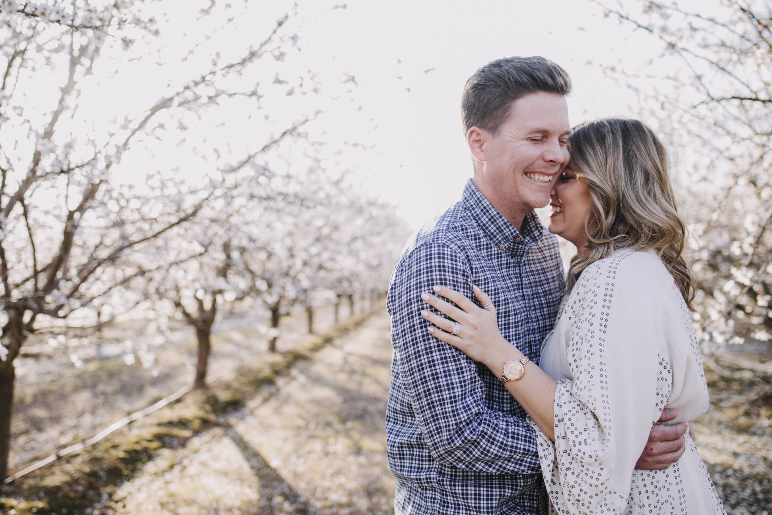 Man and his fiance candidly laughing while surrounded by blossom trees