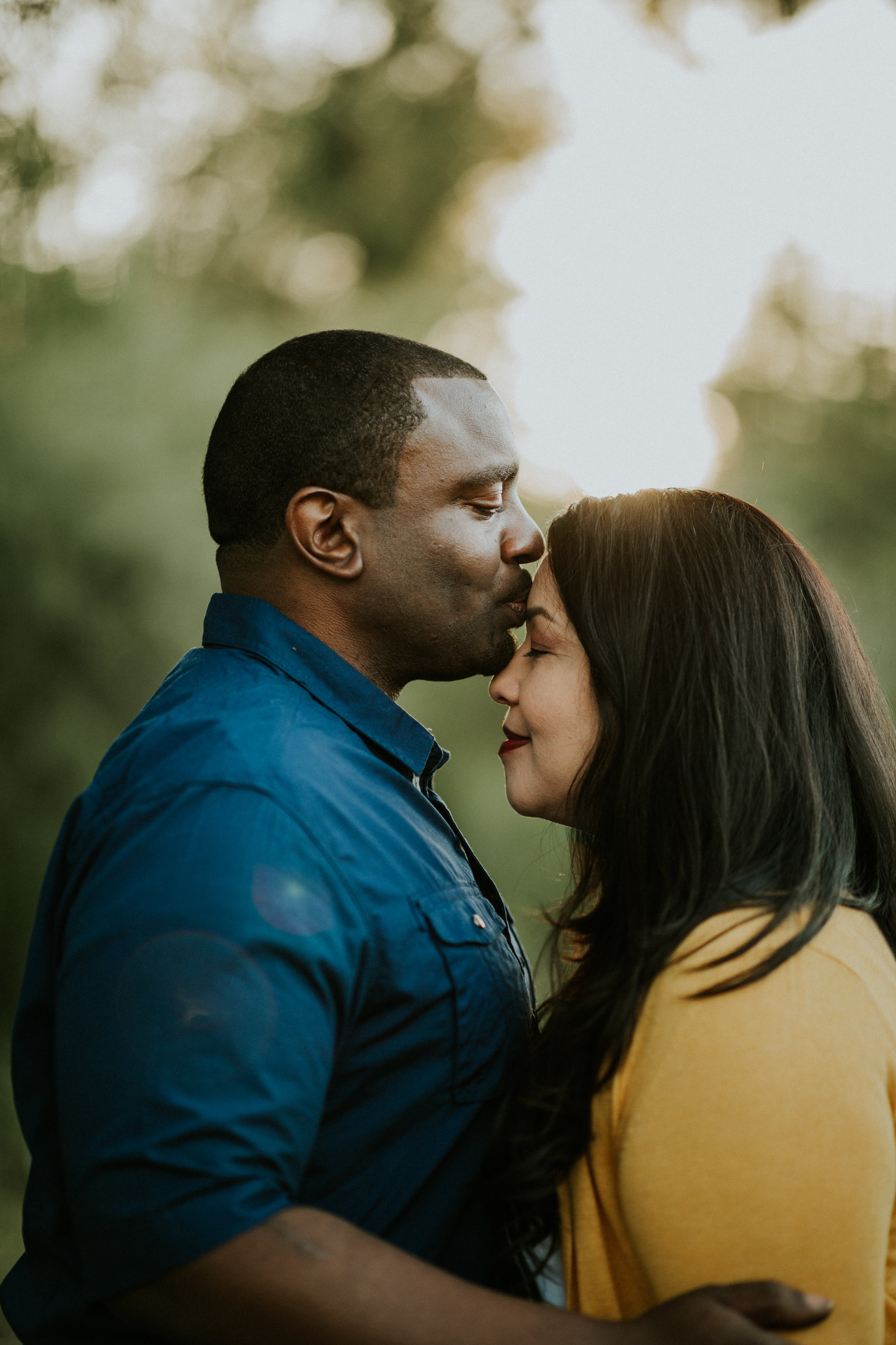 Guy kissing his fiance's forehead