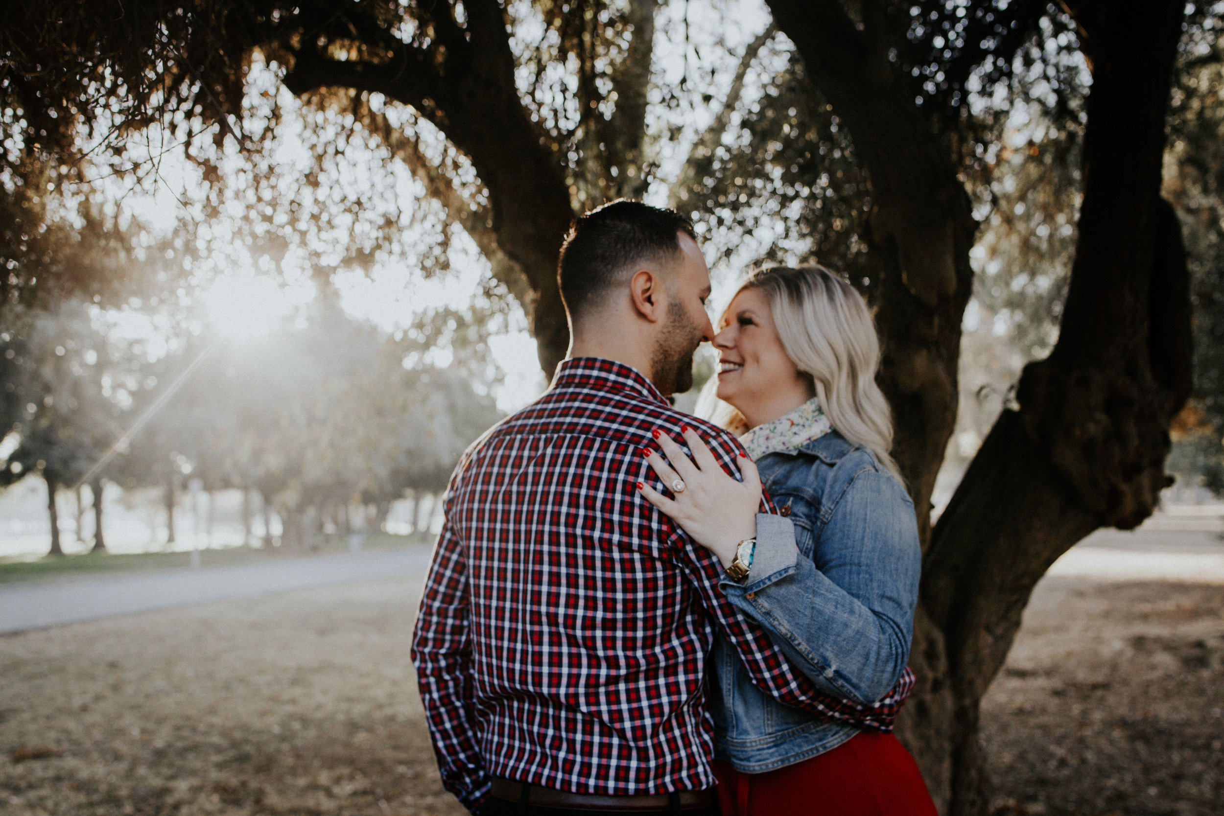 Guy and girl holding each other near tree with the sun peaking through