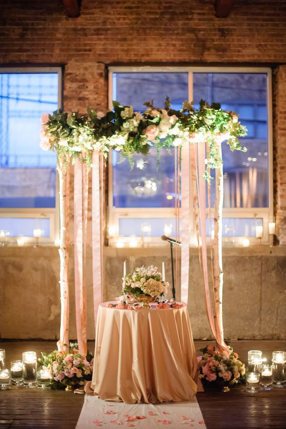 Candles, birch and flowers warm a winters wedding sweetheart table.