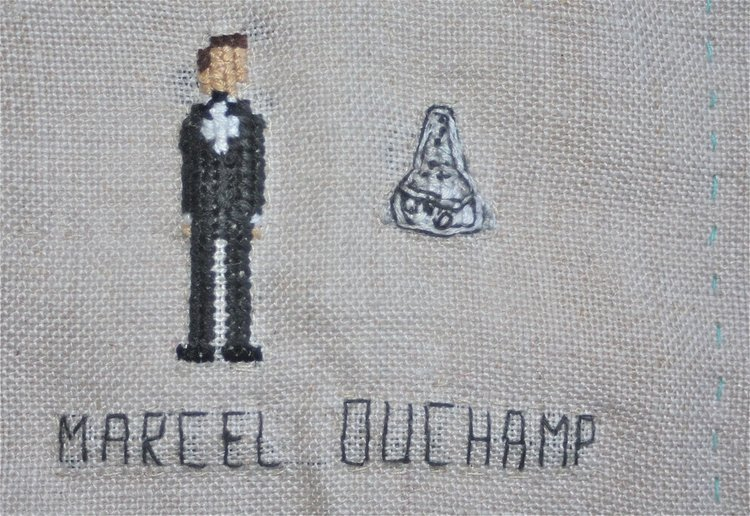 A cross-stitched rendering of Marcel Duchamp, beside his signature  Fountain  sculpture.