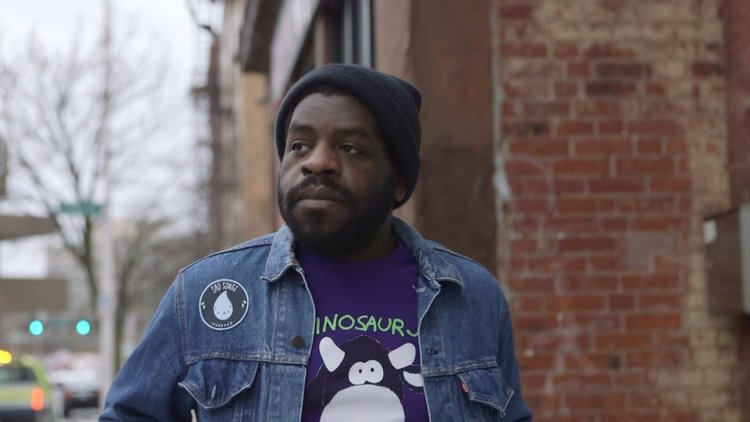 Hanif Abdurraqib walks down the street, gazing stoically into the distance.