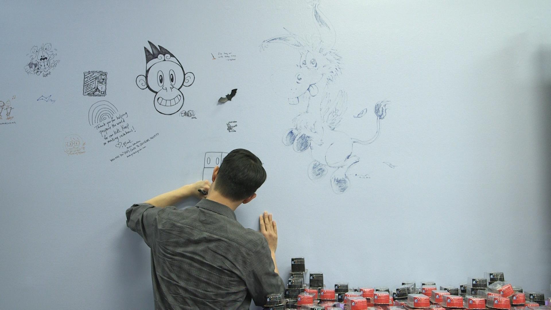 Gene Yang putting the Writing on the Walls.jpg