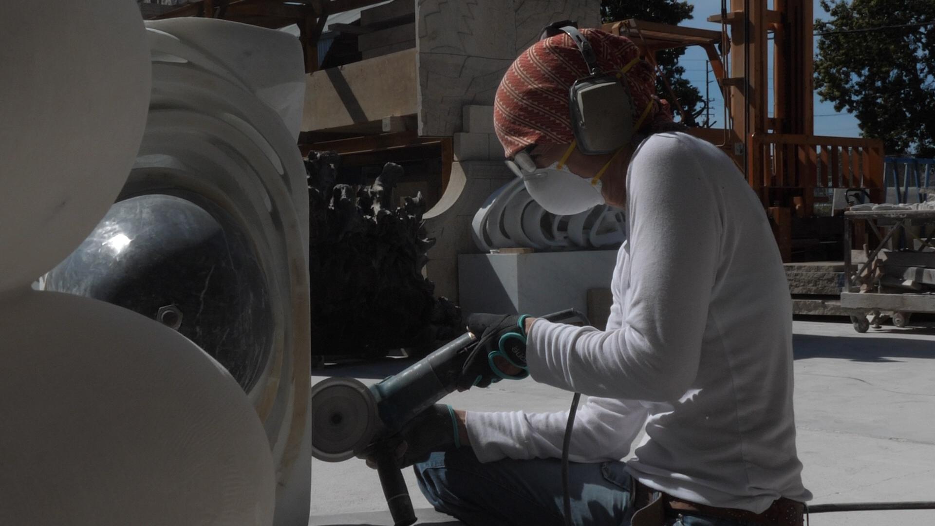 Elizabeth Turk focuses as she angle grinds a statue.jpg