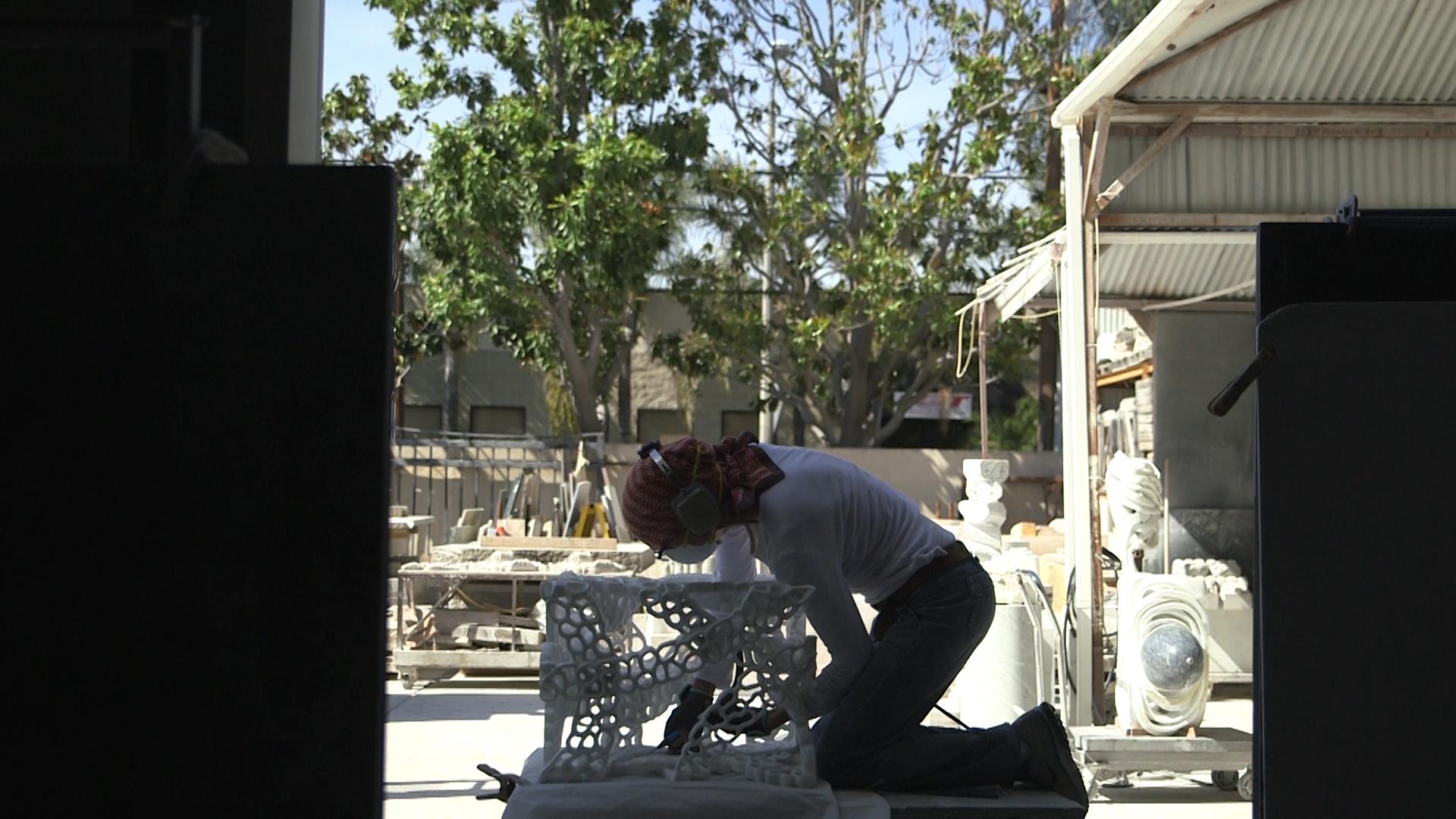 Elizebeth Turk kneels as she works on a statue.jpg
