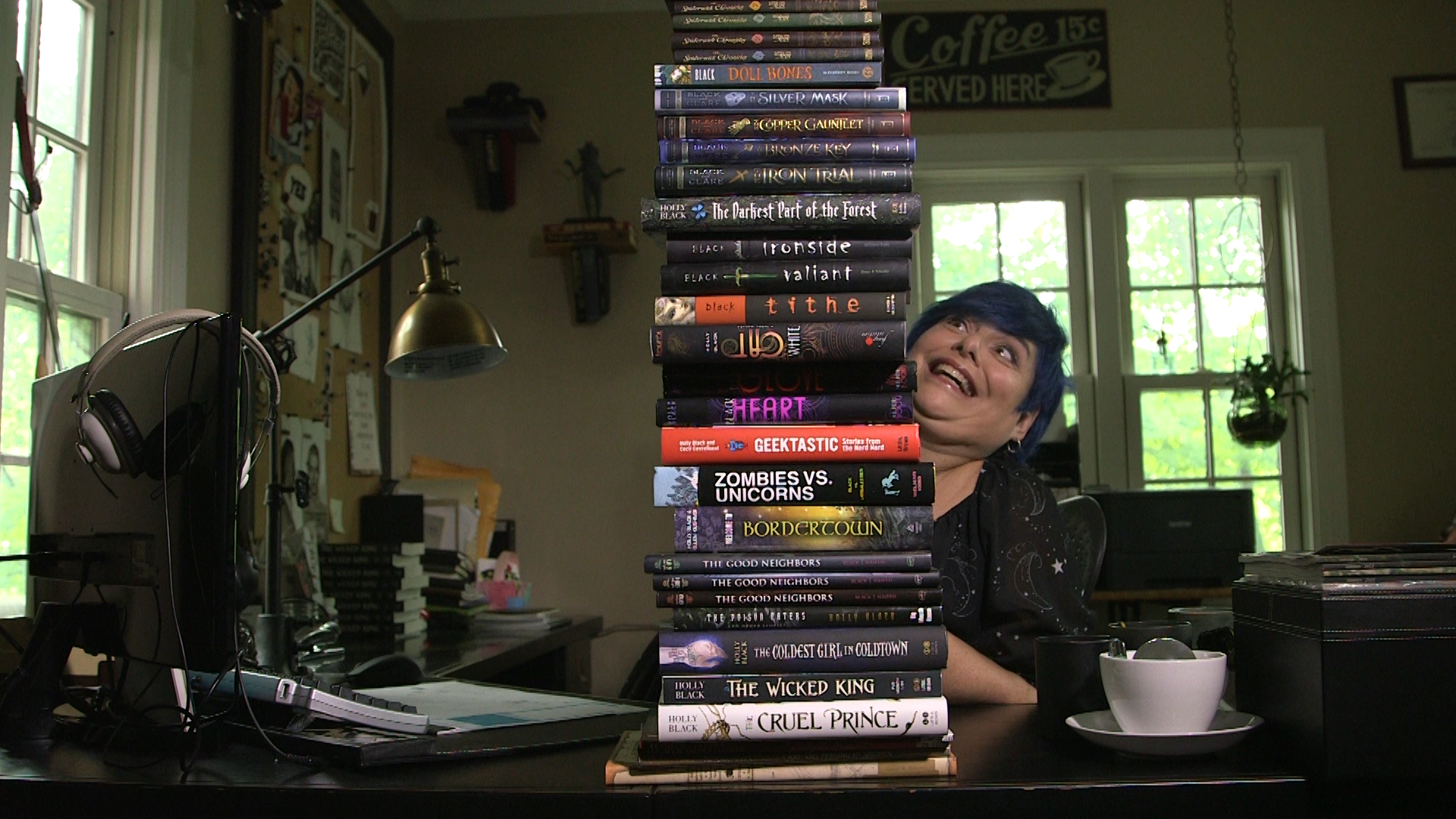 Holly+Black+looking+up+her+stack+of+books.png