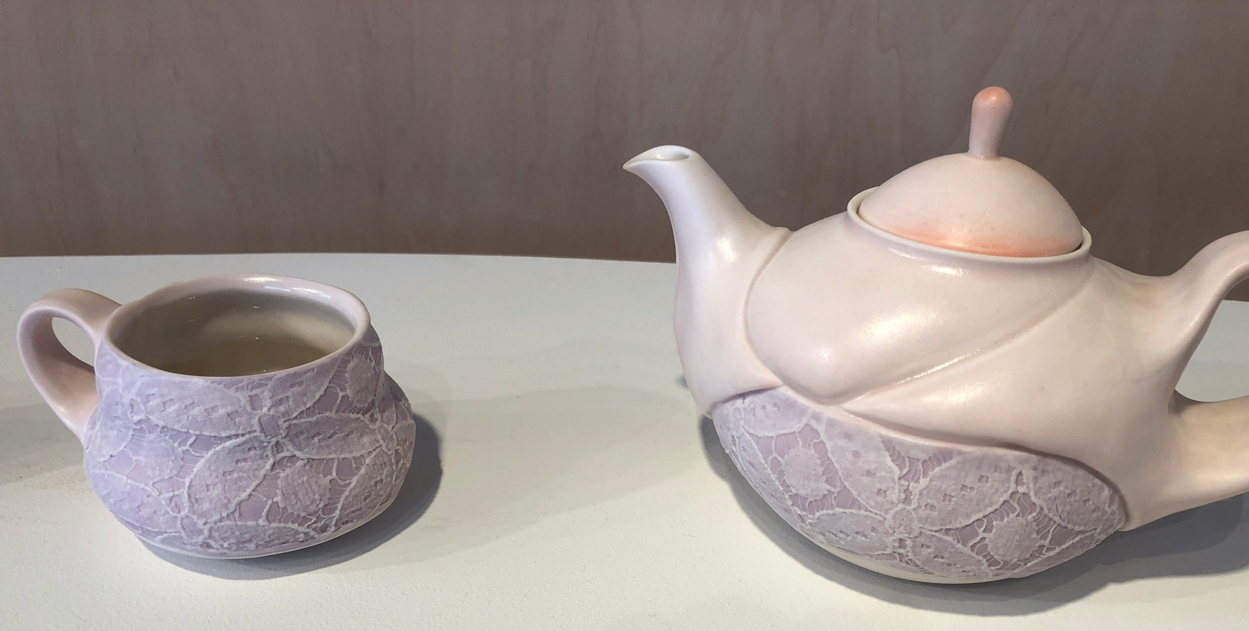 exhibition of  samantha briegel 's work, included these ceramics topped with lace.