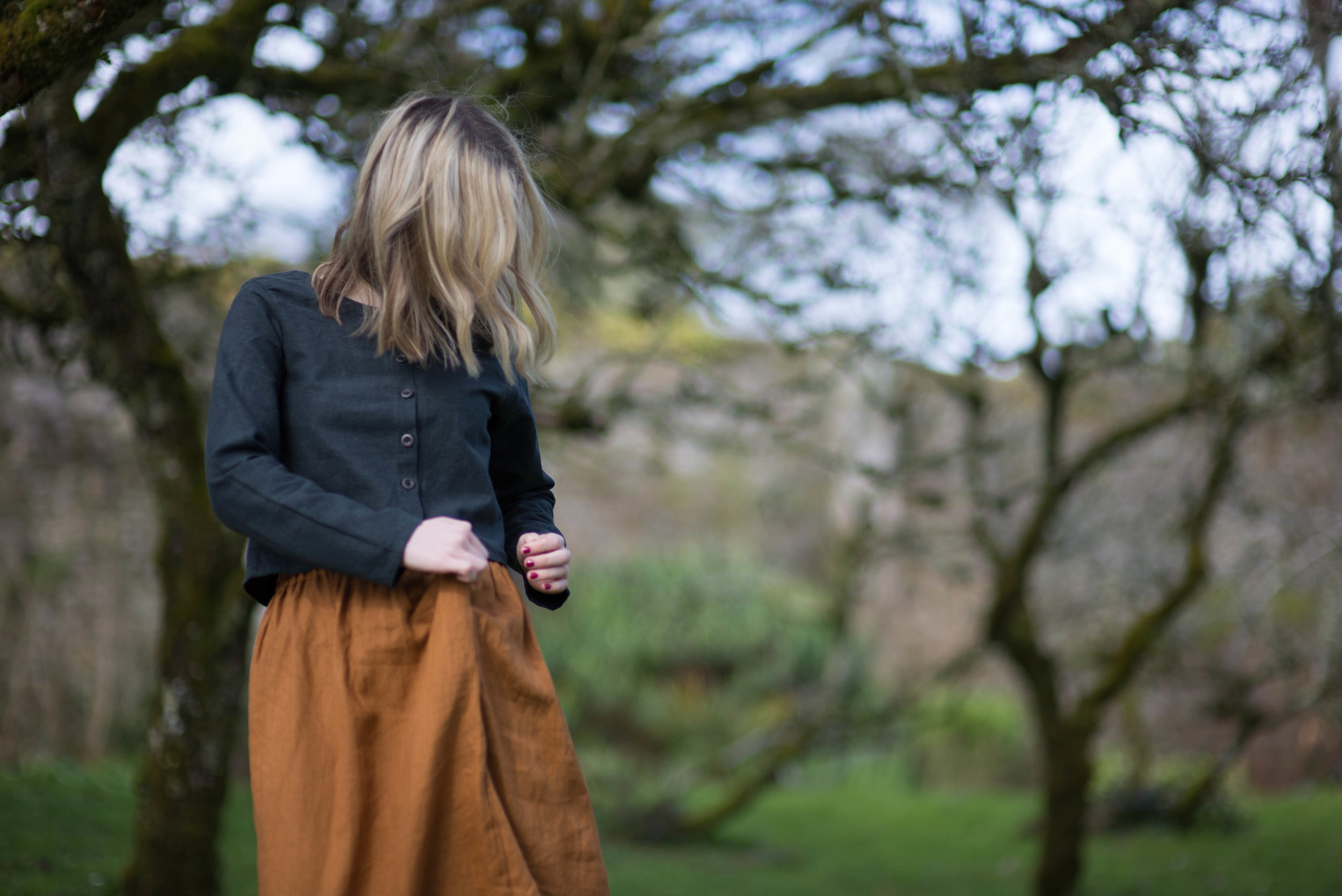 Rosie wearing the ATHENA TOP in charcoal with the ITHACA SKIRT in ochre.