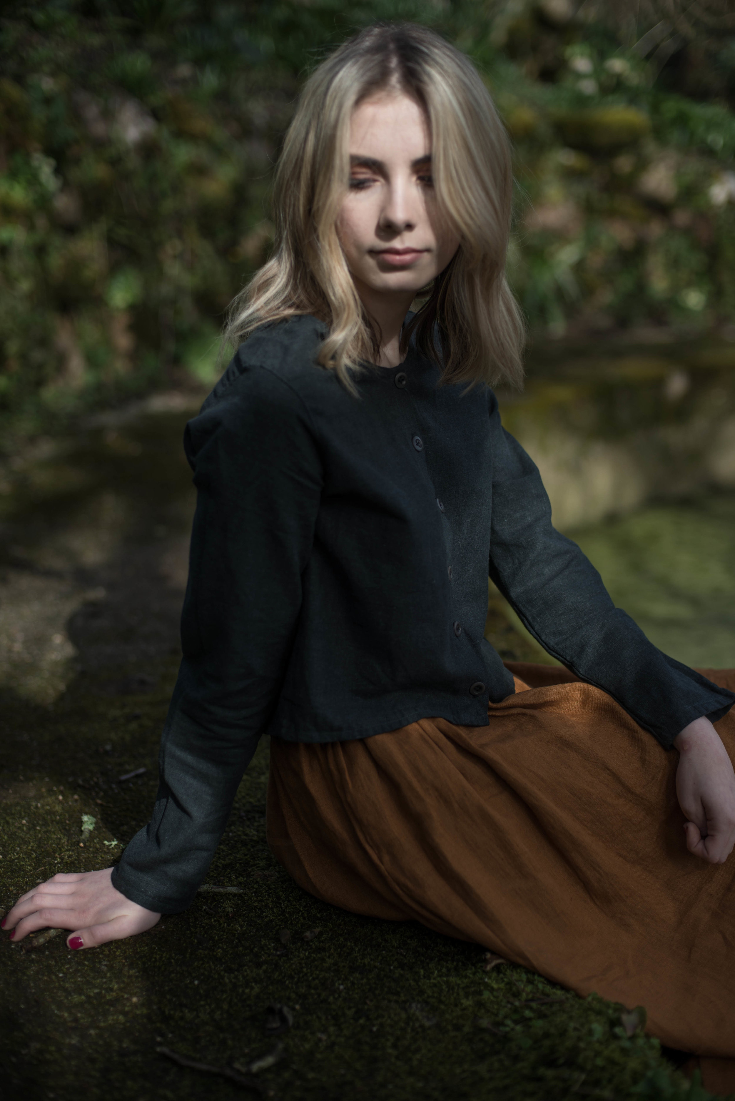 Rosie wearing the ATHENA TOP in charcoal and the ITHACA SKIRT in ochre.