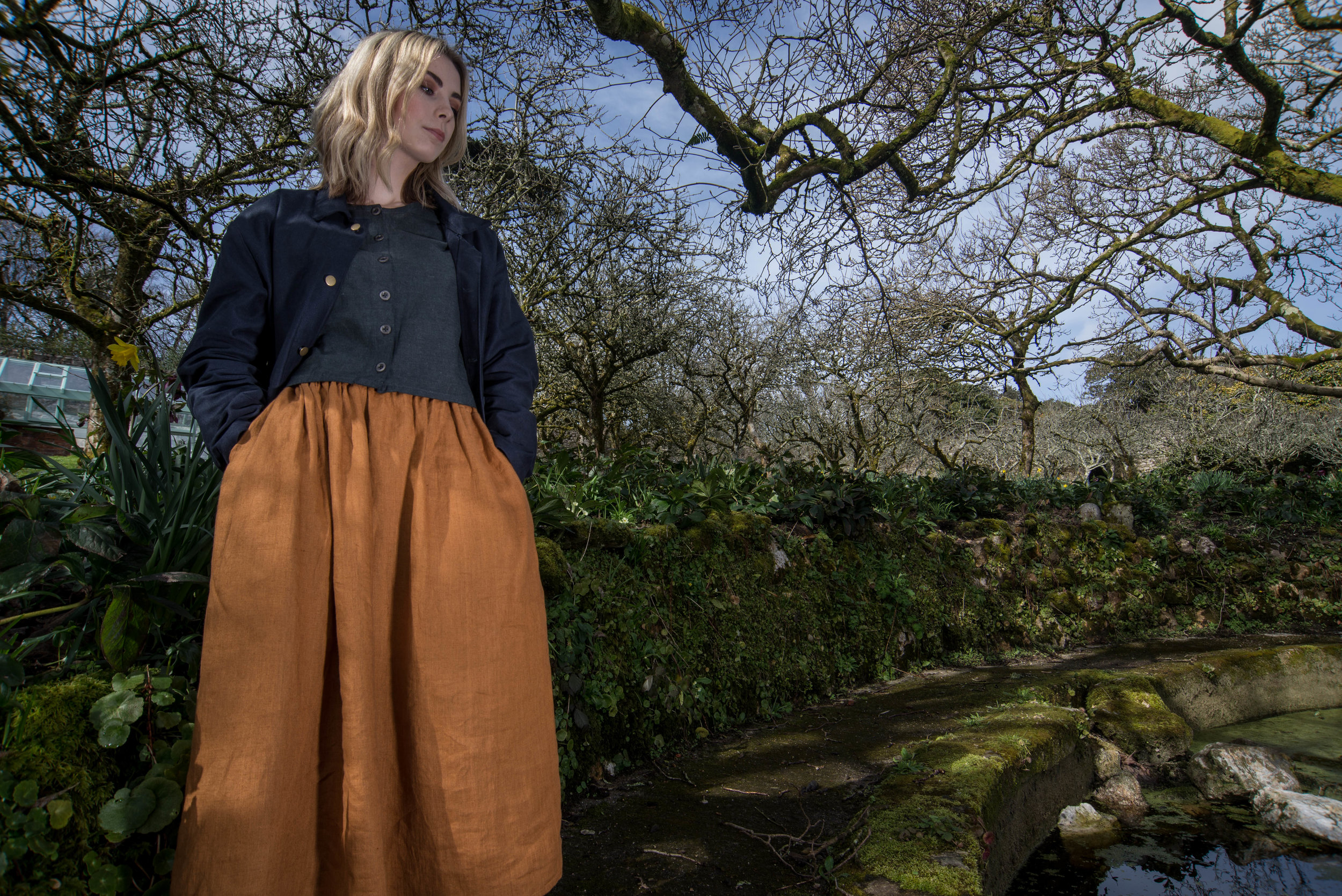 Rosie wearing the ATHENA TOP in charcoal with the ITHACA SKIRT in ochre and the WORKER'S JACKET in navy.