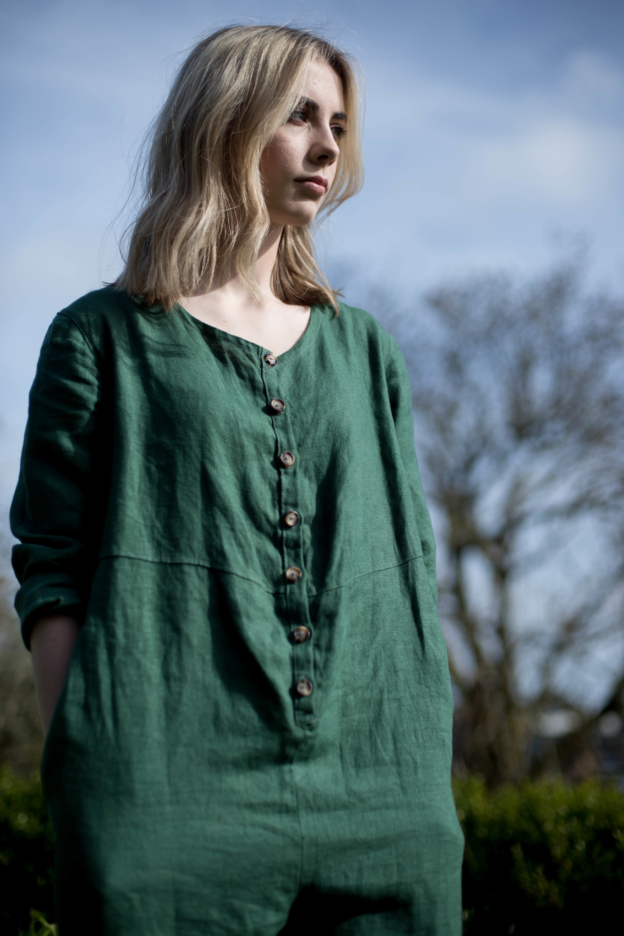 Rosie wearing the RHEA OVERALLS in green.