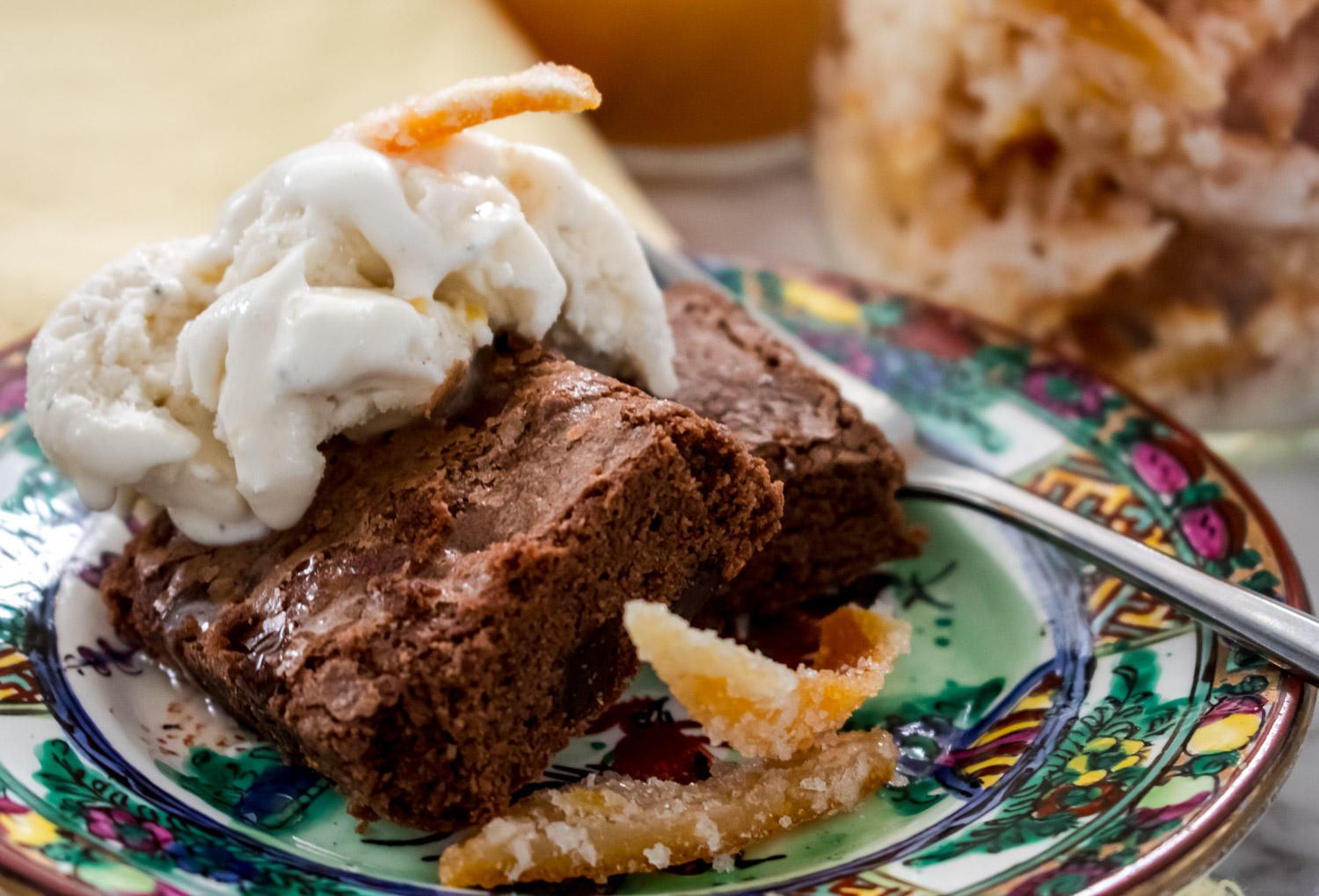 Brownies with candied orange peel topped with vanilla ice cream and whole slices of candied orange peel.