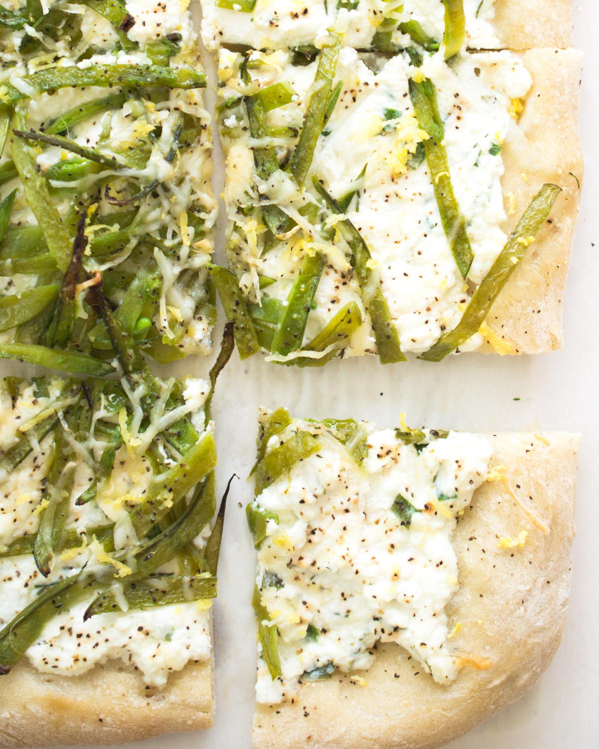 Pizza topped with herbed ricotta and sliced fresh snow peas.