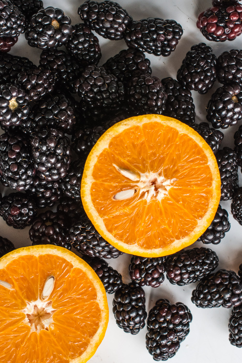 Fresh picked blackberries and an orange.